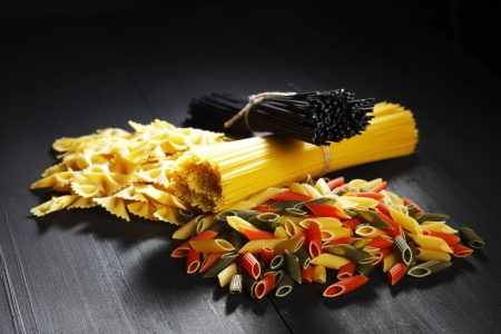 Variety of types and shapes of Italian pasta on black table photo