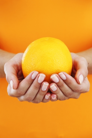 three people only: orange in woman hands close up