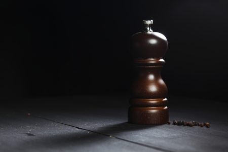 intense flavor: Wooden peppermill with peppercorns on black table Stock Photo