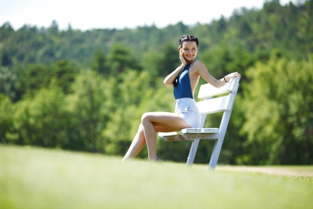 Young woman sitting on the bench in park photo