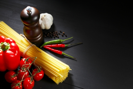 Pasta ingredients on black table, italian cuisine concept Stock Photo