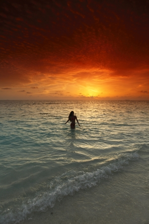 Young woman splashing in sea  under sunset light photo