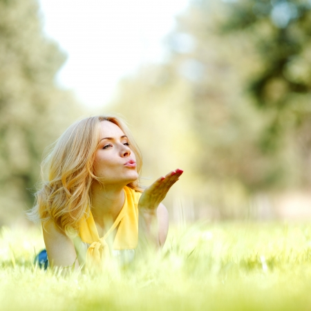 woman blowing: Happy young woman lying on grass and blowing kiss