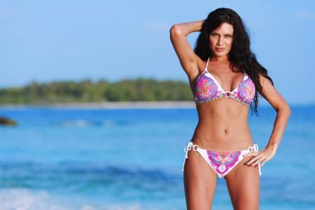 Beautiful sexy woman in bikini posing on beach photo