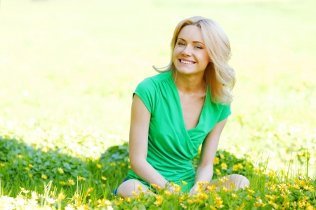 young woman sitting: Beautiful young woman sitting on flower field Stock Photo