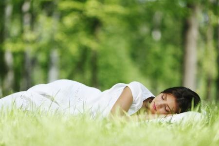 Junge Frau schläft auf weichen Kissen in frisch frühling gras