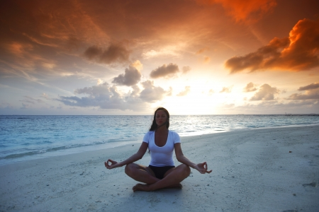 Yoga woman in lotus pose on beach at sunset photo