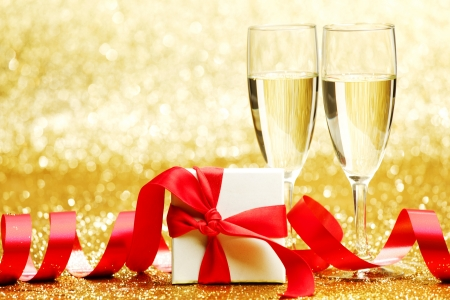 Two champagne glasses and gift on golden  photo