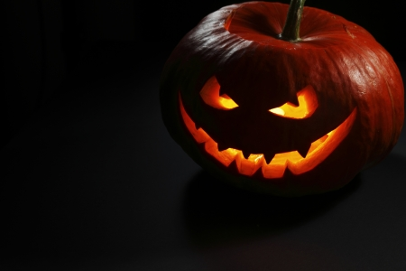 Halloween pumpkin with scary face on black  Stock Photo