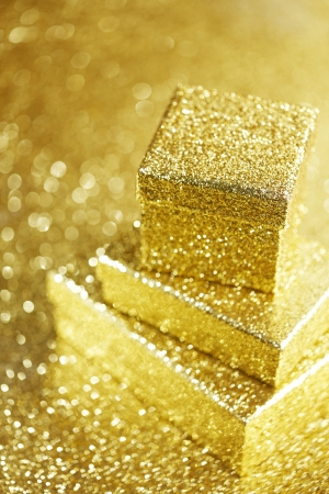 Golden boxes with holiday gifts on shiny glitter background photo