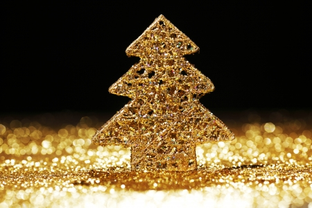 Golden christmas fir tree decoration on glitter background with black copy space photo