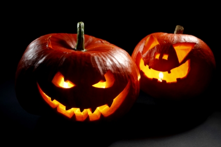 carved pumpkin: Two halloween pumpkins on black background Stock Photo