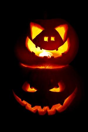 Two halloween pumpkins on black background photo
