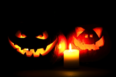 Halloween pumpkins with scary face and burning candle on black background photo