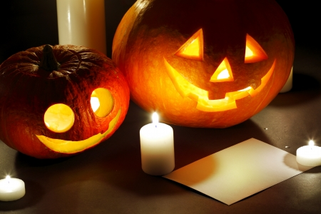 Halloween pumpkin lantern, candles and blank post card photo