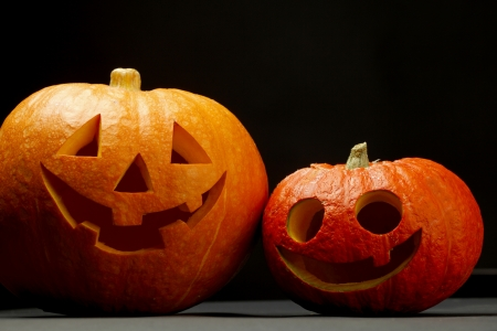 Two funny Halloween pumpkins on black background photo