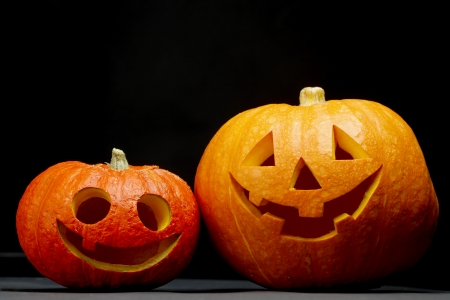 Two funny Halloween pumpkins on black background