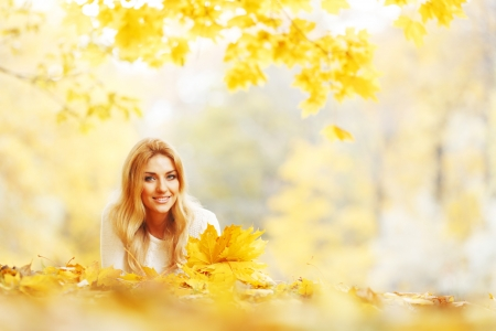 Young woman laying down on the ground covered dry autumnal foliage in beautiful park photo