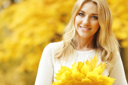 woman sweater: Portrait of a beautiful smiling woman in the autumn park Stock Photo