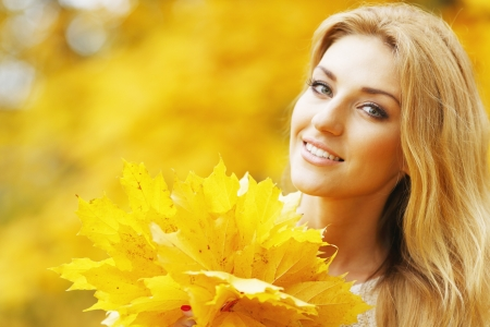 Portrait of a beautiful smiling woman in the autumn park photo