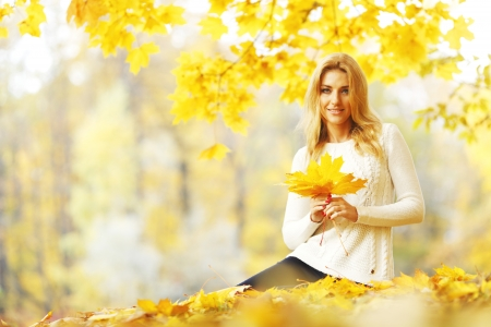 Woman sitting on the autumn leaves in park photo