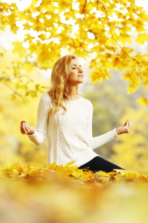 Beautiful young woman meditating outdoors in autumn park photo