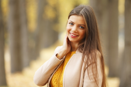 Portrait of a beautiful young woman over autumn tree  photo
