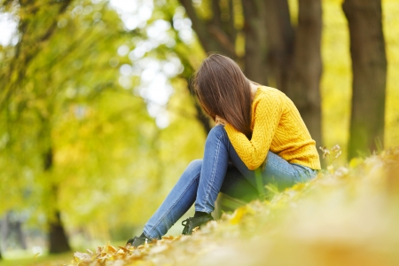 depressed woman: Beautiful woman sitting on autumn leaves in park Stock Photo