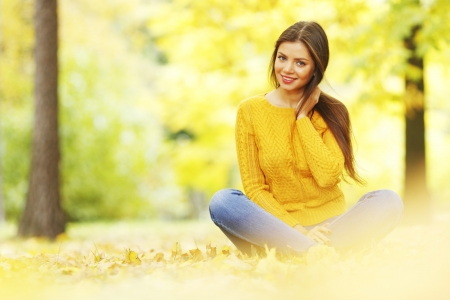 Beautiful woman sitting on autumn leaves in park photo