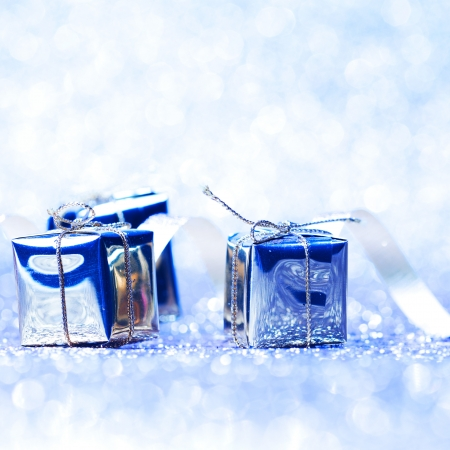 Silver christmas gifts on glitter shiny background close-up photo