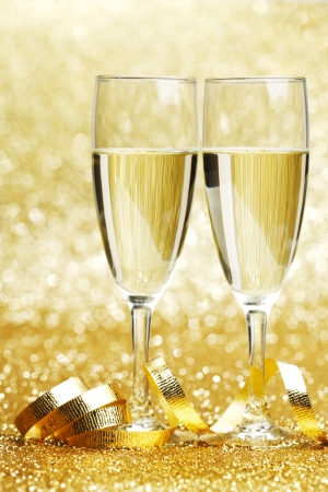 Two champagne glasses and decoration on golden background photo