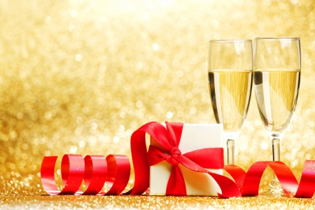 Two champagne glasses and gift on golden background photo