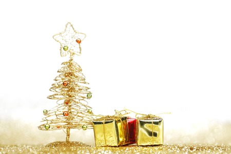 Golden christmas fir tree decoration and gifts on glitter background with white copy space photo