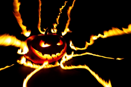 Burning halloween pumpkin on black background photo