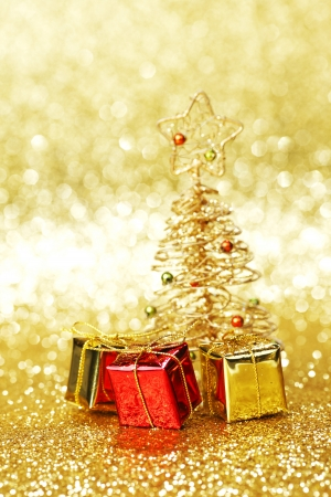 Golden christmas fir tree decoration and gifts on glitter background photo