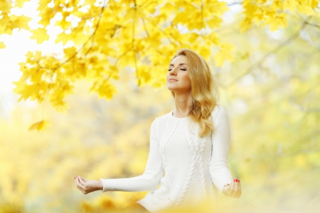 Beautiful young woman meditating outdoors in autumn park