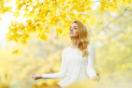 Schöne junge Frau meditieren im Freien im Herbst Park