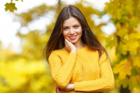 Portret van een mooie jonge vrouw over herfst boom achtergrond