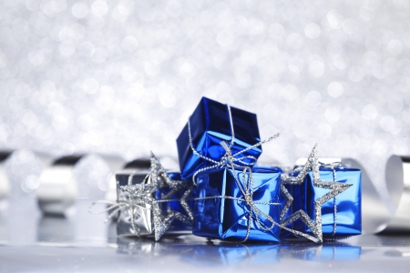 blue gift box: Christmas card with gifts and decoration on shiny silver background