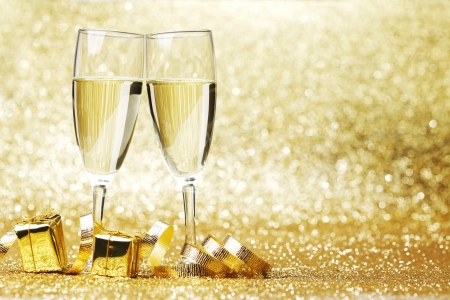 gold bow: Two champagne glasses, gifts and decoration on golden background