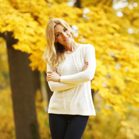 Portrait of beautiful young woman walking outdoors in autumn park photo