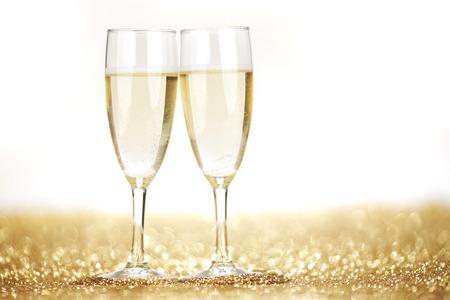 aniversario de bodas: Dos copas de champán en el fondo brillante de oro Foto de archivo