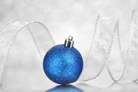silver ribbon: Beautiful shiny Christmas ball decoration on silver background