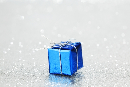 Blue Christmas gift box on shiny silver background photo