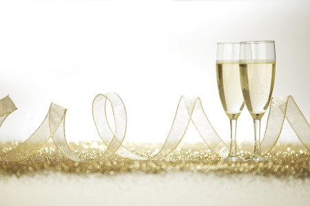 Two champagne flutes and decoration on gold shiny background photo
