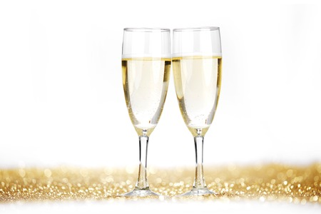 Two champagne flutes on gold shiny background photo