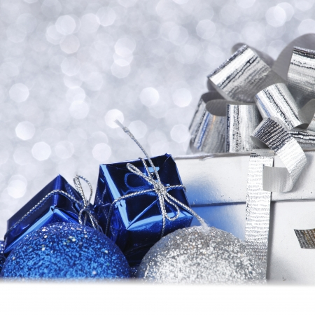 blue gift box: Christmas decorative balls and gifts on shiny silver background