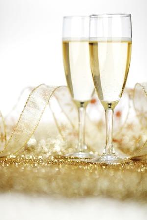 Zwei Champagner-Flöten und Dekoration auf gold glänzenden Hintergrund