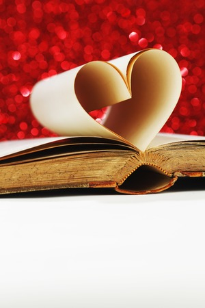 Heart made of blank pages inside a book on glitter background photo