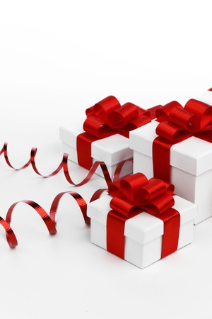 Decorative holiday gifts in white boxes with red ribbons on white background photo